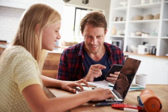 Pais se comunicando coma escola pelo computador e por um app de comunicação