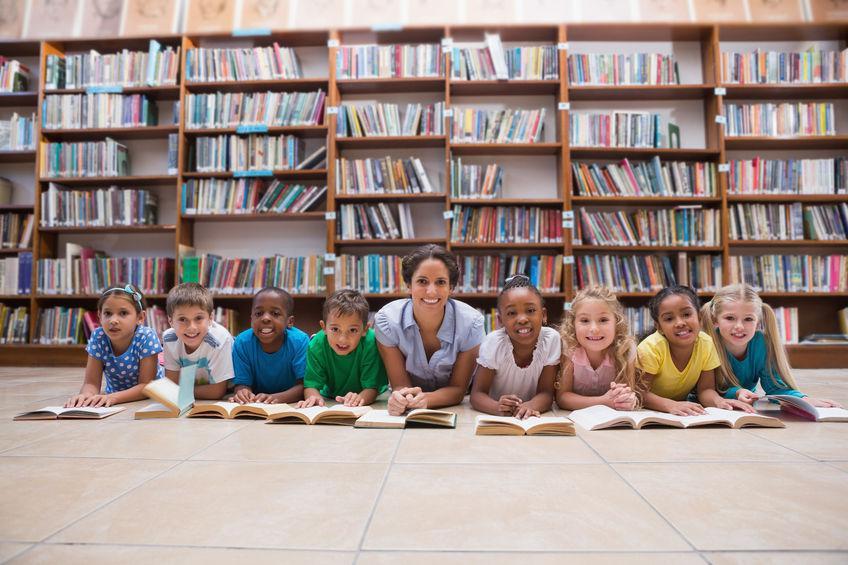 Professora com alunos em uma biblioteca. A foto ilustra post sobre otimização do espaço escolar.