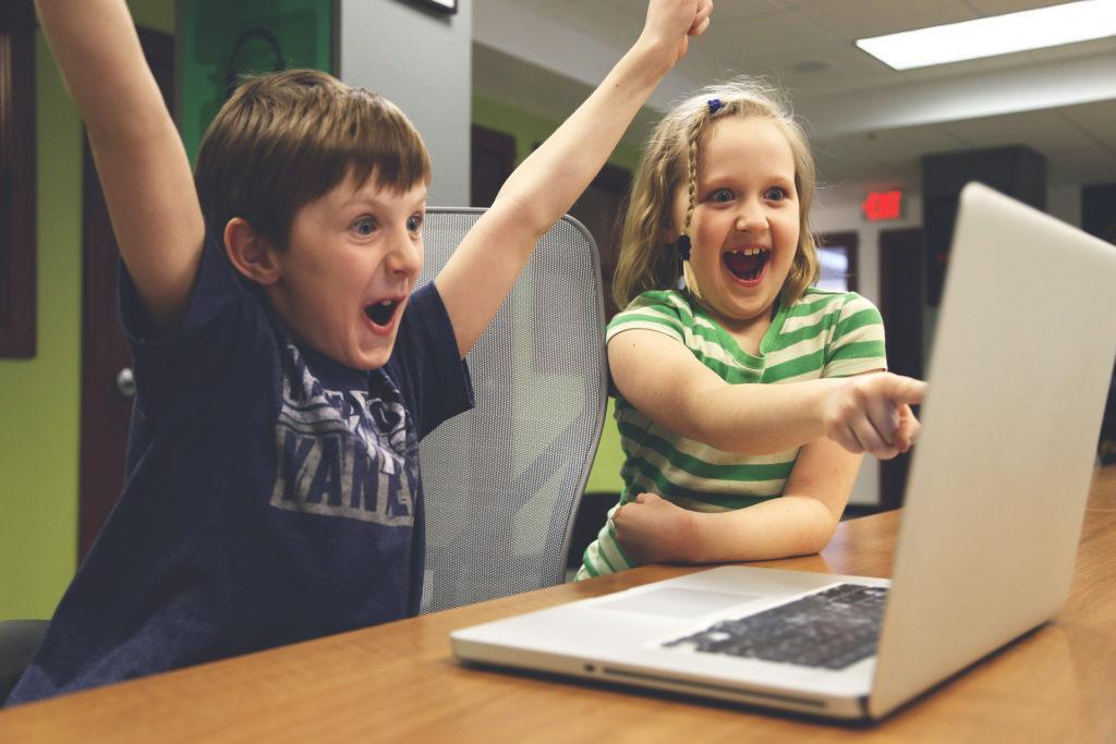 Crianças felizes em frente a um notebook. A imagem ilustra post sobre os 4 pilares da educação.