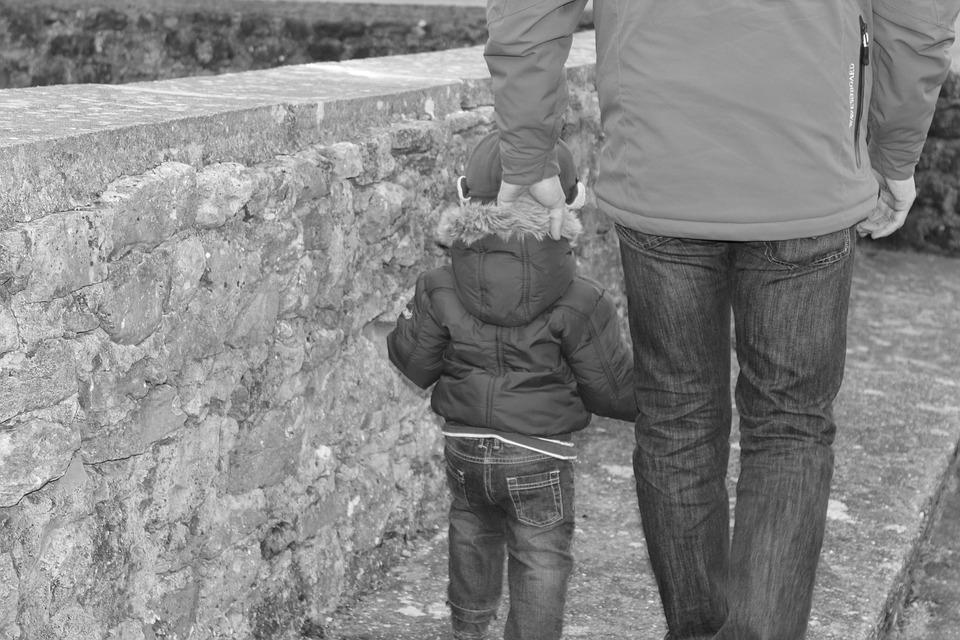 Criança andando com homem adulto do lado. A imagem ilustra post sobre segurança na entrada e saída da escola.