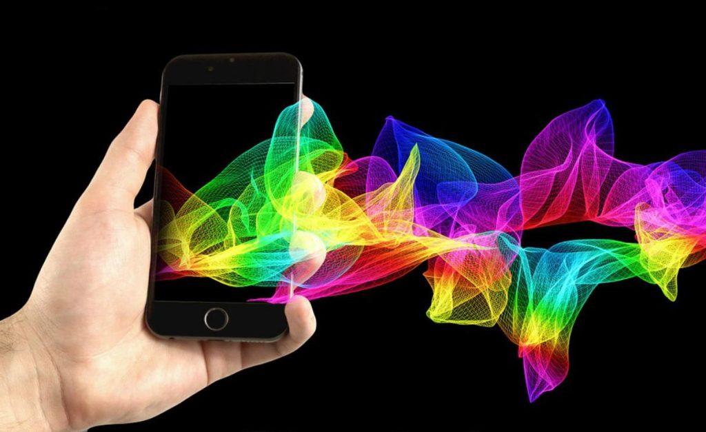 Imagem de uma mão segurando um celular, e cores saindo do aparelho. A foto ilustra post sobre comunicado aos pais.