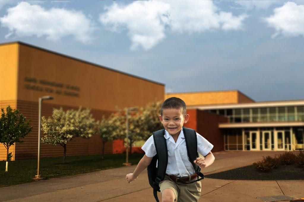 Menino correndo da escola, pois começaram as férias escolares