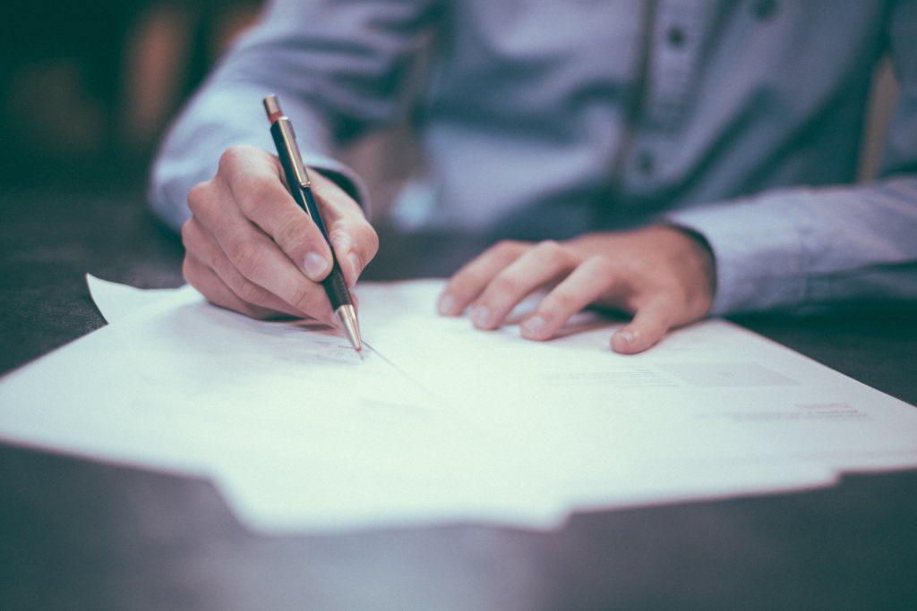Pessoa assinando um contrato de rematrícula