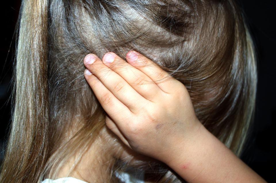 Criança vítima de bullying tapando os ouvidos