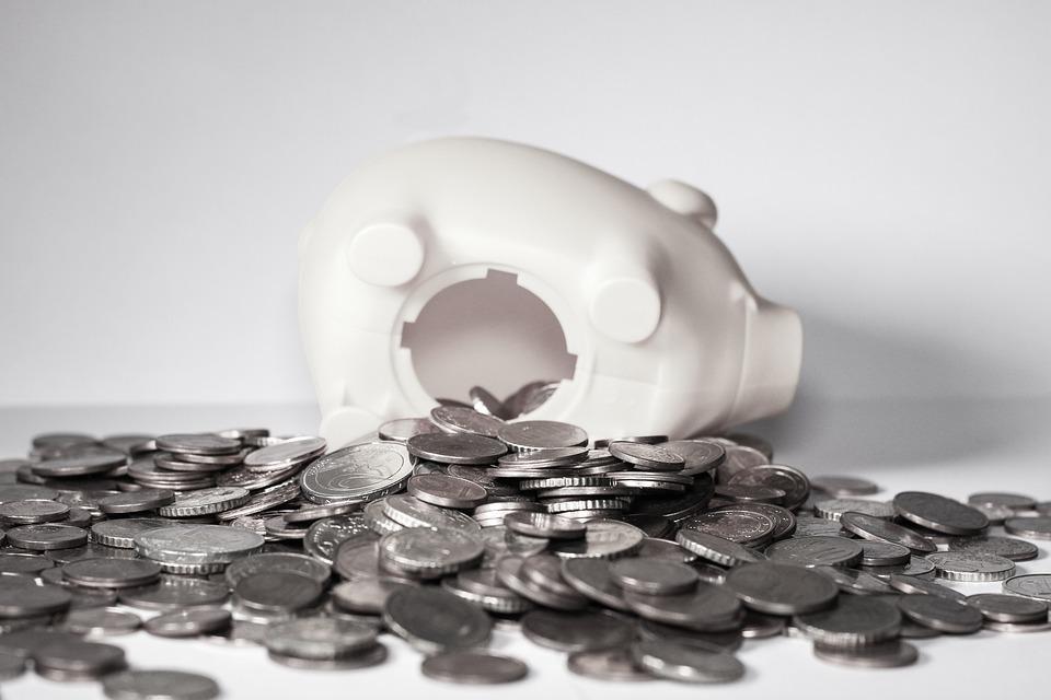 Cofrinho de porco virado com várias moedas saindo dele. A imagem ilustra post sobre inadimplência escolar.