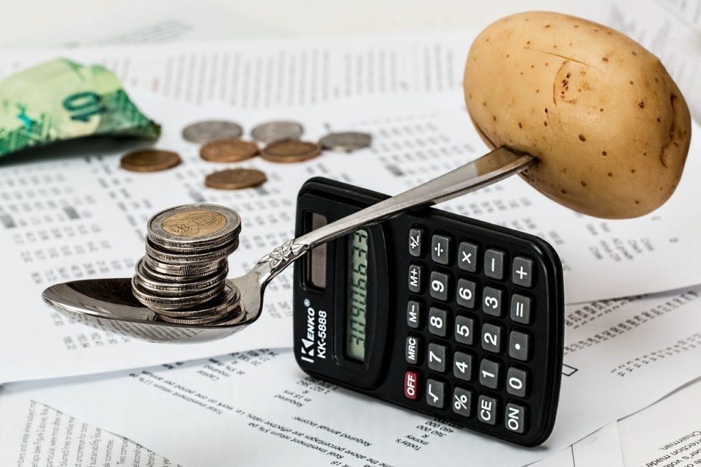 Calculadora com uma colher em cima servindo de balança entre moedas e uma batata. A imagem ilustra post sobre orçamento escolar