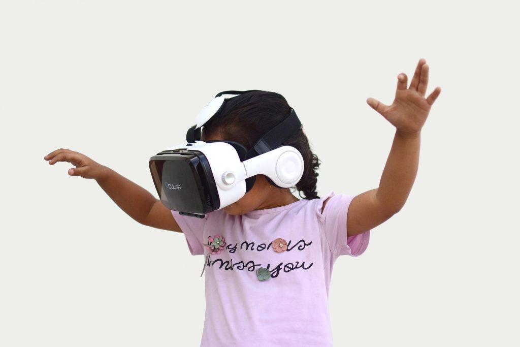 Menina usando um óculos de realidade virtual para ilustrar posr sobre aumento do rendimento dos alunos com o uso da tecnologia